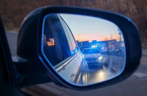 SKI  20161213. Politiet i arbeid. En politibil med blålys sees i sidespeilet på en bil i fart. NB! Modellklarert til redaksjonell bruk.  Foto: Heiko Junge / NTB scanpix