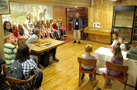 En skoleklasse på besøk i «klasserommet» på Tronstad gård. Arne Antonsen, ansvarlig for bygdesamlingen, er omviser.
