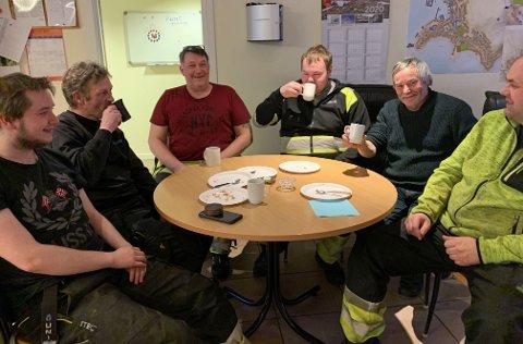 VELFORTJENT PAUSE: Tor Harald Løvland (i rødt) og brøytemannskapet tok seg en pust i bakken på teknisk etat med god mat og drikke før arbeidet med snørydding fortsetter.