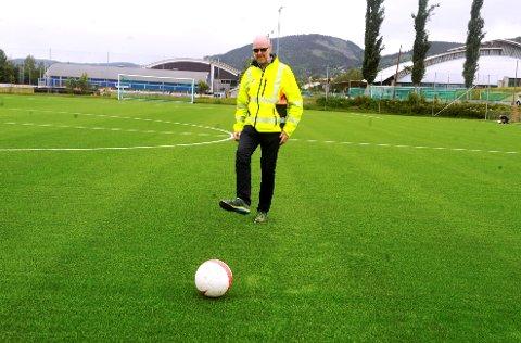 Idrettskonsulent Andrè Holen i Lillehammer kommune, skrur ballen vestover på den nye kunstgrasbanen på Stampesletta. Han lover at det også skal bli mulig å skru den østover når banen får satt seg skikkelig.
