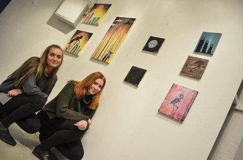 VIL NOE MER: Rikke Prang Følkner (t.v.) og Varg Kjeholt vil ta et skritt videre med egen kunst. – Vi har lyst til å vise fram det vi holder på med, sier de unge kunstnerne. Rikke har malt bildene til høyre og Varg har malt de tre lengst til venstre. Foto: Anja Lillerud