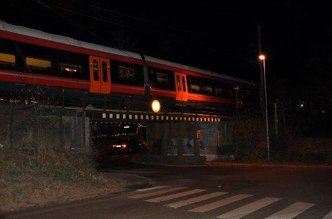 Toget har stoppet like før Sandefjord stasjon og står blant annet over overgangen over Dølebakken.