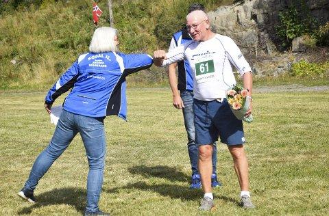 FIKK BLOMSTER: Odd Lars Bredal ble hedret av Kodal ILs Inger Johanne Riis Tollnes for sin mangeårige løpeinnsats.