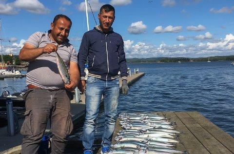Mohammed Jaafar ( til venstre) og Hasan Aobed er fornøyd med å ha fått 80 makrell på tre timer.