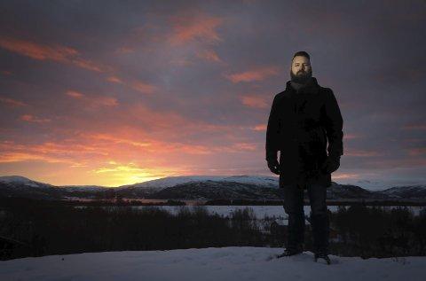 Hjemme i Valnesfjord: Simon Flack har et utkikkspunkt på tomta. Selv ute i periferien er han bare noen tastetrykk unna hele verden. Foto: Tom Melby