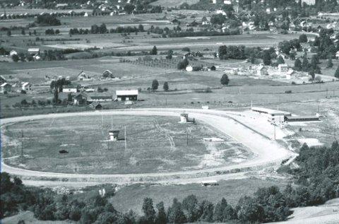 1955: Flyfotoet viser travbaneområdet som ligger relativt ensomt til på et jorde på Åssiden. Banen er sett fra Drammen og oppover til Nedre Eiker. Løpstårn og andre installasjoner var flyttet fra travbanen på Marienlyst som ble nedlagt seks år tidligere. Foto: Drammen byarkiv