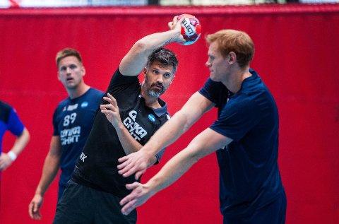 Viser vei. Trener Kristian Kjelling. Hovedtrener Drammen HK. Drammenshallen. viser hvordan han vil ha det, mens Espen Gommerud Våg (t.h.) forsøker å stå i veien.