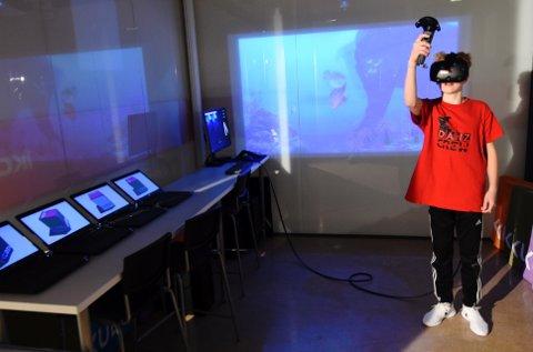 ÅPNET KUBEN: Tirsdag ettermiddag var Tage Hogness (15) en av de aller første som kunne prøve «Kuben» i Lillehammer bibliotek. Midt i vinterbyen Lillehammer kunne han gå på havets bunn og nesten ta på en hval. – Dette var kult. Tenk hvis det kommer mange kule spill der det går an å bruke kontroll på, sier Hogness.Foto: Knut Storvik