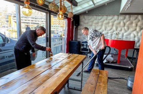 KLARGJØRING: Med gjenåpning på fredag beises bordene og gulvet støvsuges. Fra venstre:  Rune Bræck og  Kurt Atle Lind Iversen.