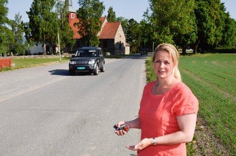 SENTER: Kirkeverge i Hole, Julie Ulven, vil bygge et kirkesenter ved trærne til høyre bak henne. Hun håper samtidig at trafikkforholdene kan bli bedre ved kirken.