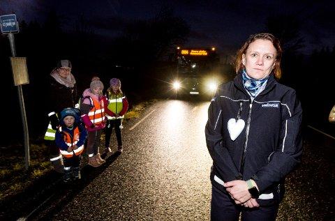 Bussjåfør Mette Edvardsen deler ut gratis reflekser til barna hun kjører. (fv) Sander Olai Slettmoen Alme, mamma Tone Slettmoen Alme, Sara Othilie Slettmoen Alme,  Lena Edvardsen, (foran) Mette Edvardsen