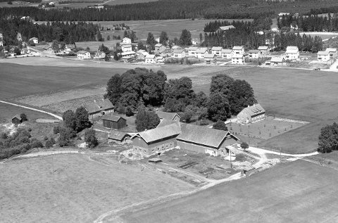 Fra 1902: Husebylåven (foran i bildet) ligger i et verneverdig kulturmiljø på Skedsmokorset. Bildet viser gården slik den så ut i 1955, men stedet framstår som på bildet. Hele fjøsdelen (bygget over teglsteinsmuren) er nå tatt ut av planene. Foto: Schröder/Widerøe/MiA