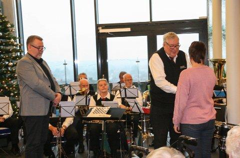 PENGEGAVE: Øyvind Klemetsen (t.h.) g dirigent Christer Clausen i Sarpsborg veterankorps overrekker pengegaven til daglig leder i Varmestua Sarpsborg, Annika Filtvedt.