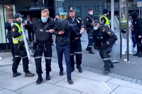Her ble en av de pågrepne ført bort av politiet. Totalt 14 personer ble sendt i arresten etter opptøyene.