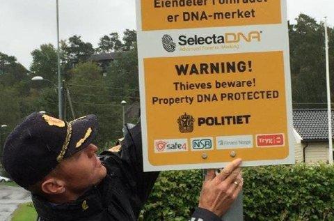Odd Kostveit, politiinspektør i Sandefjord henger opp et skilt som viser at innboet i boligene i Hasleåsen er sikret med syntetisk DNA.
