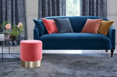 Velur egner seg godt til å dempe lyd. Her er både sofa, puter og puff i samme materiale, og teppet gjør også en god jobb i så måte.