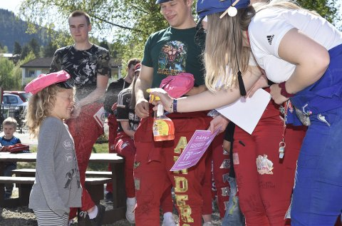 DØPT: Russepresident Erik Kvendset Andersen og medruss Elise Stensønes døper Ellen Helgetun Schei med en sprut med farget vann under den høytidelige rosarussedåpen i Midtigrenda barnehage i Surnadal torsdag 16. mai.