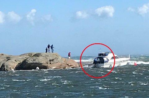 REDNINGSAKSJON: Fem eller seks personer jobber på spreng med å redde båten.