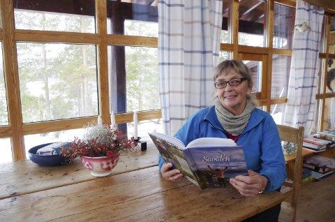 VED SJØEN: Ingveig Vangen på hytta der Savalen vises mellom furuene i bakken utenfor. Nå er boka hennes ferdig. Foto: Tonje Hovensjø Løkken