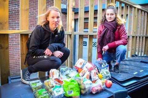 GOD FANGST: Hanna Kjernsby i Naturvernstudentene og Iris van Brunschot i Fremtiden i våre hender viser frem matvarene de fant i en søppelkasse ved en butikk i Ås. - Mye fullt spisebar mat kastes på grunn av dato eller skade på emballasje, sier de.