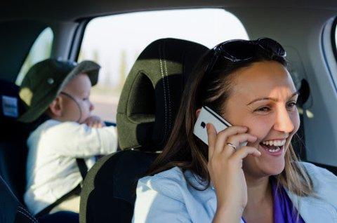 Mobiltelefon i hånden og utålmodige barn i baksetet er en dårlig kombinasjon i sommertrafikken. Illustrasjonsfoto: Colourbox