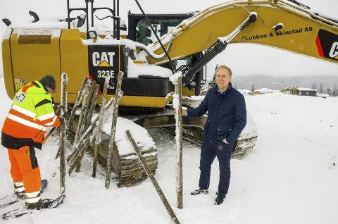 TOMTEMERKER: Wiggo Smedberg følger ivrig med mens mannskaper fra Entreprenør Lobben & Skinstad AS gjør klar stolpene som skal merke sentrum av hver eneste nye tomt i Melumenga.