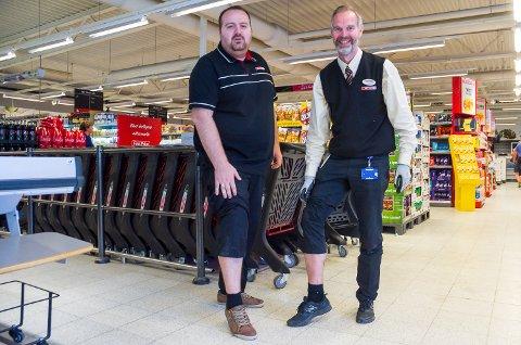 KUN FOR FOTOGRAFEN: Hverken Jeton Seferi (t.v) eller butikksjef Lars Petter Herseth savner shorts på jobben, men drar opp buksatil ære for fotografen. Det synes Bygdepostens lesere er helt greit – shorts på jobb er ok i varmen.