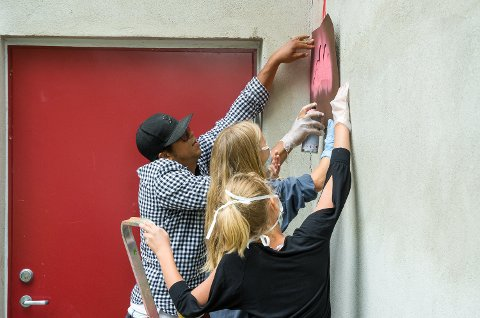 GODT I GANG: Hailey Michelle Jahr Thon og Thea Regine Grøterud Lehmann får god hjelp av gatekunstner Rodrigo Vitorio Lisboa Souza til å spraye maling inn i sjablongen.
