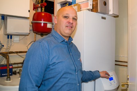 EFFEKTIV: Martin Grøterud Lehmann viser fram husets ferske varmepumpe, som på effektivt vise sørger for god varme i huset til en rimelig pris.