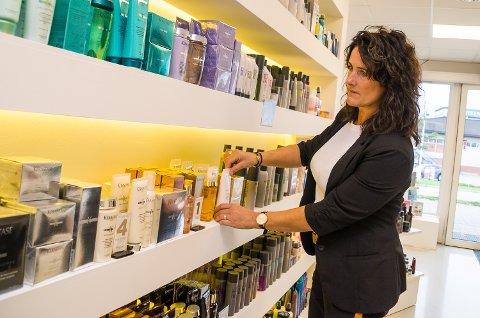 DRIVER GODT: Merete Krokvik Hartz bedyrer at Finess hårstudio driver godt, til tross for et mindre minusresultat i fjor. – Det er regnskapstekniske årsaker, sier hun, mens hun sorterer litt i utstillingshylla.