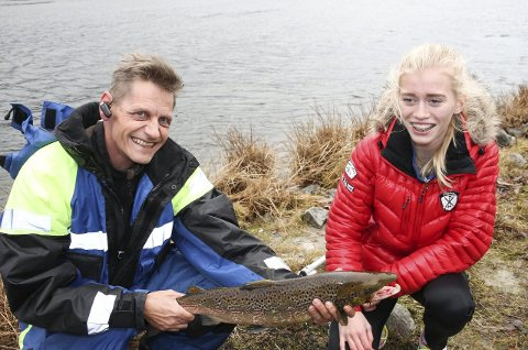 Lykkelig fisker: Hedda Sandvik har fått en laks på 2,5 kilo og synes det er veldig bra at Per Saastad trår til og holder laksen for henne.