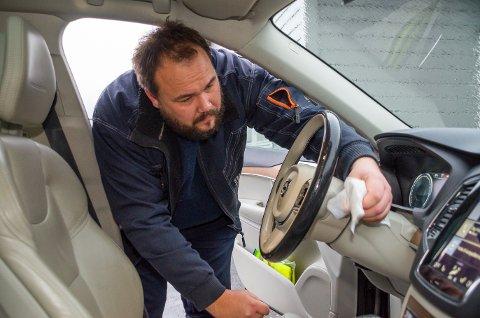 VASKER: Dag Kristian Moen Hæhre er nøye med renholdet av skolebilene. Her tar han en ekstra runde på ratt og hendler.