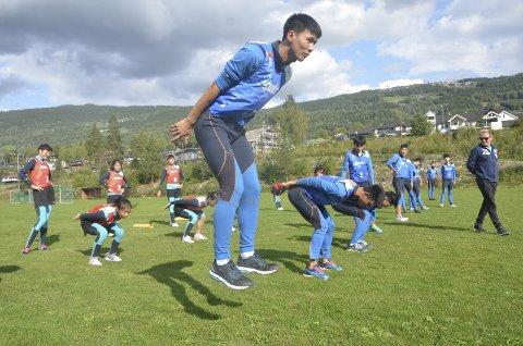 BARMARKSTRENING: De 22 ungdommene fra Kina under trening på Øyer idrettsplass. De er slapp gjennom nåløyet i Kina fordi de har spesielle forutsetninger til å bli gode skihoppere. Til høyre ser vi sportslig leder for prosjektet, Kjetil Strandbråten.