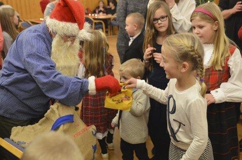 """NISSEN PÅ PLASS: Selvsagt troppet julenissen opp da alle sang """"På låven sitter nissen"""". Her er det Ingeborg Dæhlen som er heldig og får en godtepose."""