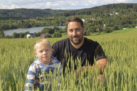 VENTER PÅ VARMEN: Kornbonde Iver Ulven på Grindvoll og sønnen Ola håper på en varm og lang høst for at kornet skal bli best mulig. På dette jordstykket dyrker 36-åringen hvete.
