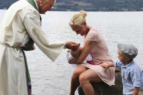 SPENT: Storebror Walter følger med mens Astrid Ines Bernström får tre håndfuller fjordvann over hodet. Fadder Mika Jägerstedt holder barnet.