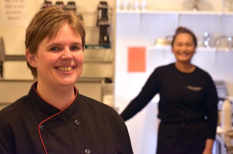 SJEF: Kjøkkensjef Ann-Helen Åbråten trives best på kjøkkenet. I bakgrunnen kollega Saijai Nimomrom.