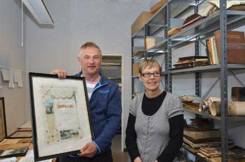 Låg i uthuset: Jan Reidar Tokheim og Siri Jordal med et av Knud Knudsen sine mange diplomer. Samlingen han låner ut til NVIM inneholder blant annet ukjente fotografier fra Knudsen sin reise til Amerika. – Dette er stort, sier Jordal, arkiveringsansvarlig ved museet.