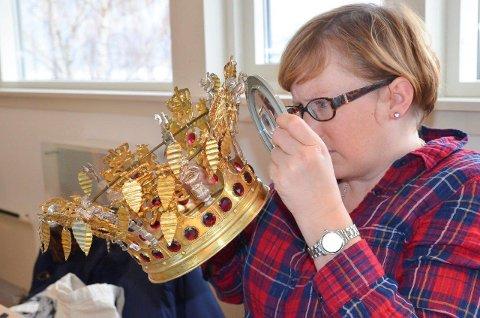 Under lupen: Camilla Rossing sjekker stempler på den forgylte brurekronen  de daterer til 1848. Her er Kristian 7. s monogram, riksløver med krone og haner som symboliserer fruktbarhet.