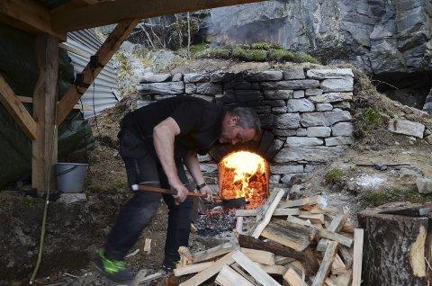 Fyrbøter: Torfinn Hus passer på at ovnen mates med furuved. Brenneprosessen trenger temperatur på 850 grader.