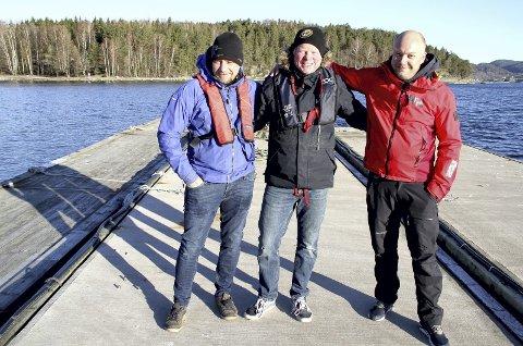 Ny giv: (Fra v.) Sverre Hagen, Dag Rune Nilsen og André Hafsås står på bølgebryteren som skal erstatte den medtatte brygga til venstre. I bakgrunnen Kommersøya og Kommersøysundet. Foto: Lars Ivar Hordnes
