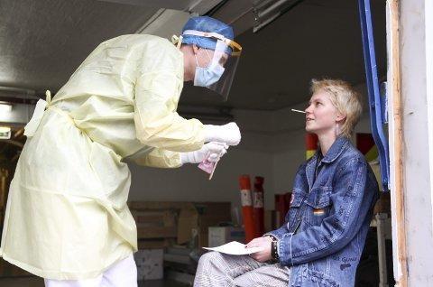 TOK TESTEN: Helene Solberg testet seg for mulig korona-smitte i Holmestrand onsdag ettermiddag. – Jeg har vært forkjølet. Det er årsaken til at jeg ønsker å teste meg, sier Solberg. Tester er lege Andreas Thunes. Han tok prøver både fra munnen og nesa. Foto: Lars Ivar Hordnes