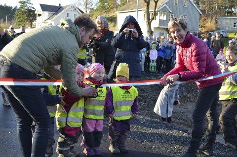 Åpnet: Den nye gang- og sykkelstien ved Neslandstunet i Kroken ble åpnet torsdag. Her får ordfører i Drangedal, Tor Peder Lohne hjelp av Sigtru Nesland og noen av de fremmøtte barna.