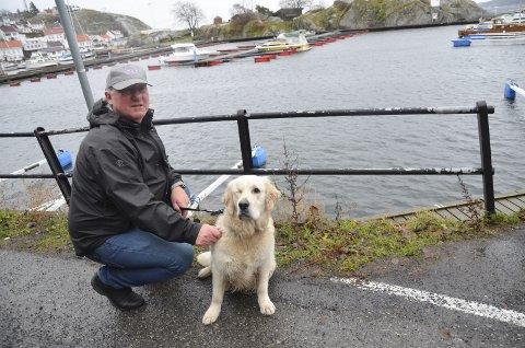Her: Jan Einar Schulze (55) og Golden retriveren Charlie (1) på Barthebrygga. Mannen de reddet opp av vannet lå og klamret seg til brygga der den er merket med tallet 11.