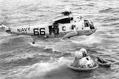 KONSEKVENSER: Dette bildet viser kapselen med Apollo 11-crewet etter at de landet i havet med redningsarbeidere på vei ned. Her er kapselen enten akkurat åpnet, eller på vei til å bli åpnet.