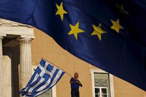"""A protester waves a Greek flag at the entrance of the parliament building during a rally calling on the government to clinch a deal with its international creditors and secure Greece's future in the Eurozone, in Athens, Greece, in this June 22, 2015 file photo. Greece is due to make a 1.6 billion euro debt repayment to the International Monetary Fund (IMF) this week.     REUTERS/Yannis Behrakis/Files  GLOBAL BUSINESS WEEK AHEAD PACKAGE - SEARCH """"BUSINESS WEEK AHEAD JUNE 29"""" FOR ALL IMAGES"""