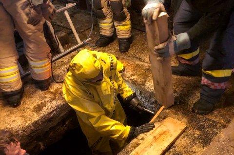 Mannskap fra brannvesenet på veg ned i møkkjelleren.