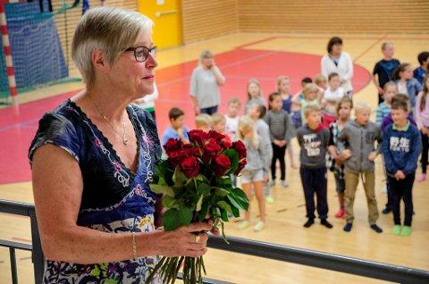OVERRASKET OG RØRT: Avtroppende rektor Marit Rismyhr på Kråkstad skole fikk overrakt roser fra alle klassene, og det var en rørt og glad dame som ble takket av. (Foto: Kari Kløvstad)
