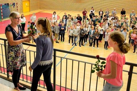ELEVENE TAKKET: Representanter fra alle klassene overraskte roser til Marit Rismyhr, som nå takker for seg etter 37 år som rektor på Kråkstad skole. (Foto: Kari Kløvstad)