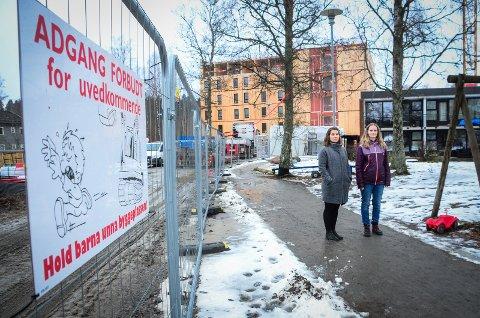 """TETT PÅ: Lekeplassen ligger """"vegg i vegg"""" med byggeplasen. Karoline Brekke Lauvrak og Kristiane Fagerli sier at de føler det utrygt å ha barna lekende ute med anleggsmaskiner og lastebil"""